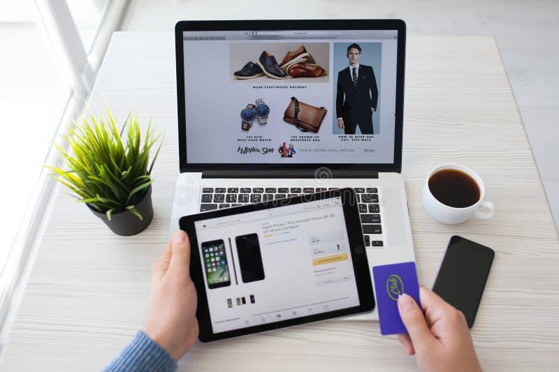 Equipe manter um iPad pro com as Amazonas em linha do serviço da compra imagens de stock royalty free