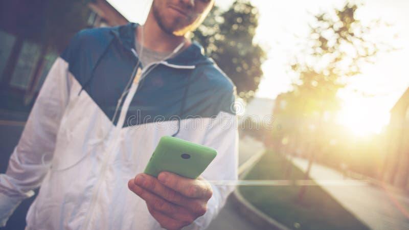 Equipe a mensagem de datilografia em seu telefone celular e o passeio na rua no por do sol imagens de stock