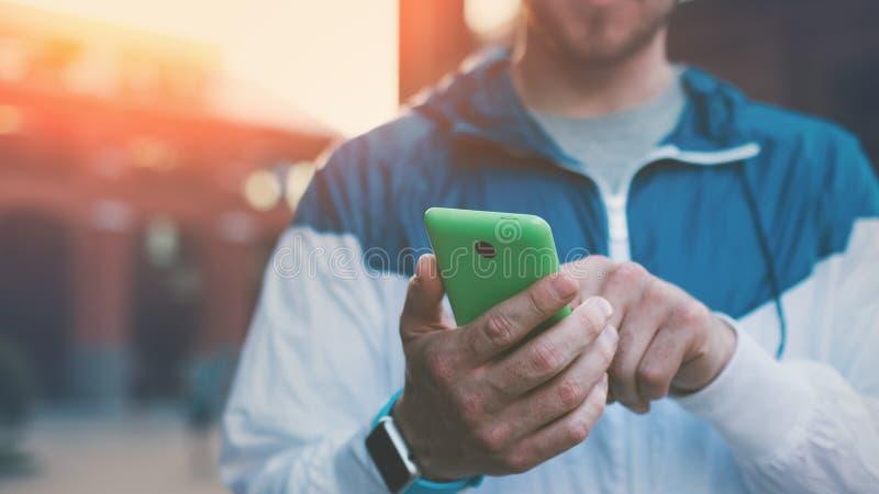 Equipe a mensagem de datilografia em seu telefone celular, por do sol na rua foto de stock