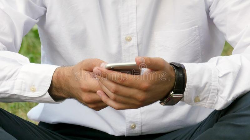 Equipe a mensagem de datilografia no telefone esperto no parque Foco nas mãos imagem de stock