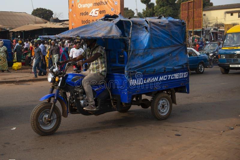 Equipe a montada de seu triciclo do motor na frente do mercado de Bandim, em Guiné-Bissau fotos de stock