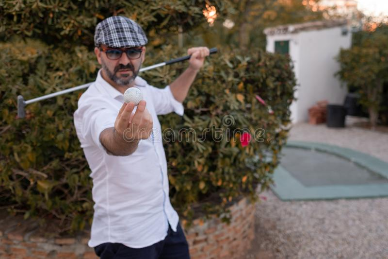 Equipe mostrar a bola de golfe em suas mãos com o clube de golfe no seu para trás imagem de stock