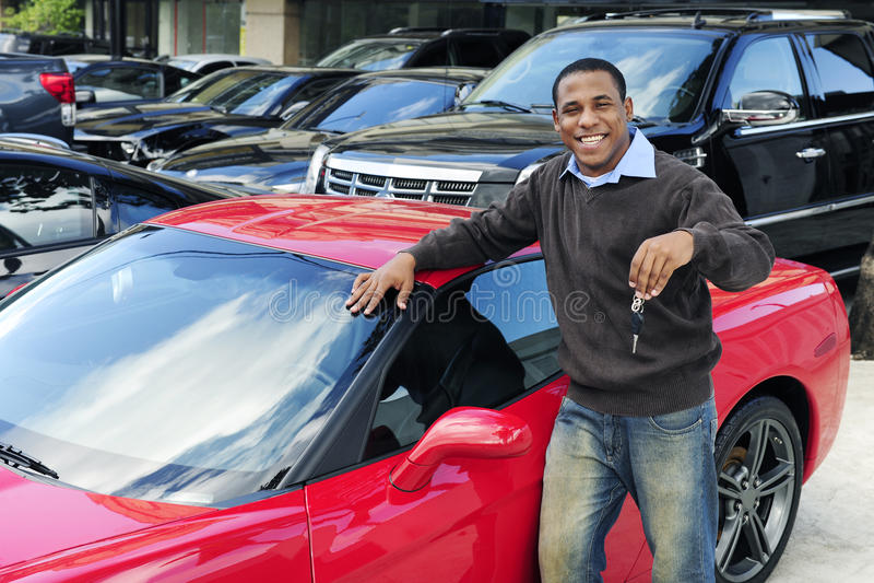 Equipe mostrar a chave do carro de esportes vermelho novo foto de stock