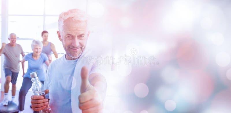 Equipe mostrar os polegares acima do sinal com os povos que exercitam no fundo fotografia de stock royalty free
