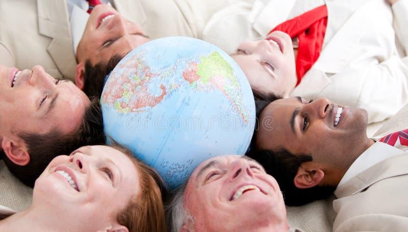 Equipe Multi-ethnic do negócio que encontra-se em torno de um globo foto de stock royalty free