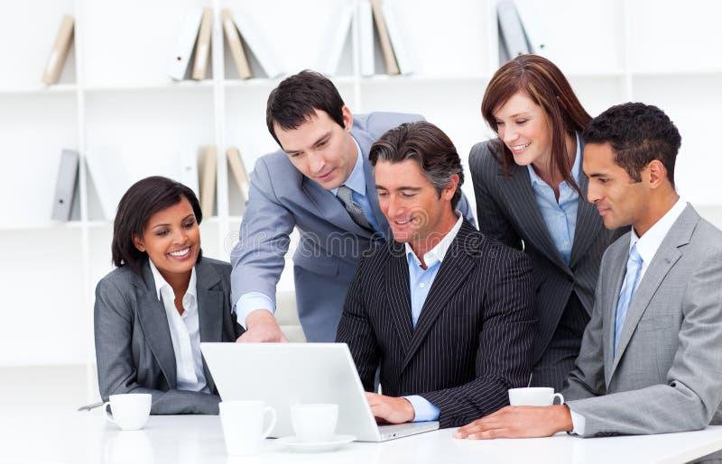 Equipe multicultural do negócio que olha um portátil imagem de stock royalty free