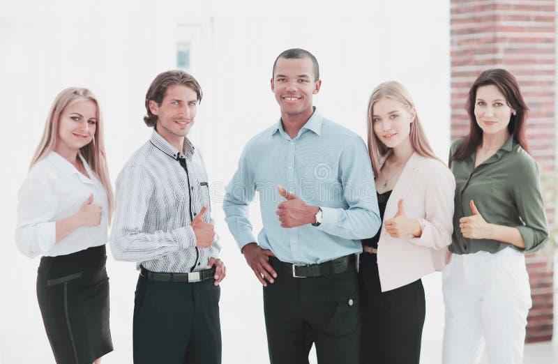 Equipe multinacional bem sucedida do negócio que mostra o polegar acima fotos de stock royalty free