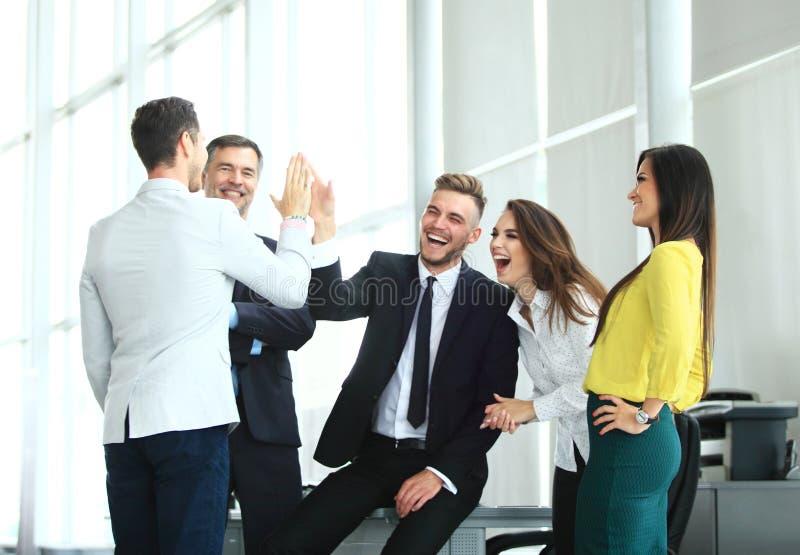 Equipe multirracial bem sucedida feliz do negócio que dá um gesto dos pífanos da elevação como ri e elogio seu sucesso fotografia de stock