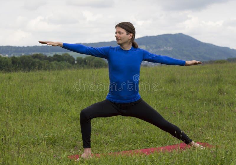 Equipe na pose do guerreiro II durante a ioga fora imagens de stock royalty free