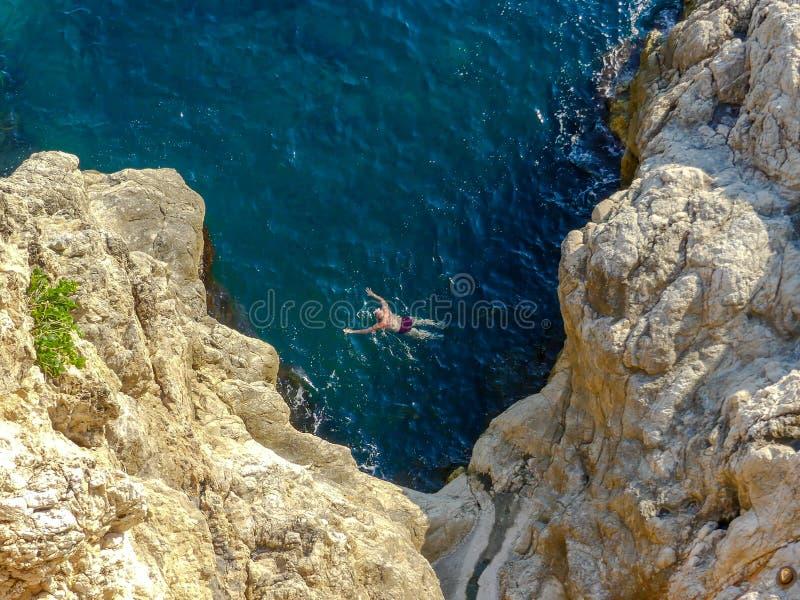 Equipe a natação na água aberta perto dos penhascos fora das paredes velhas da cidade de Dubrovnik fotos de stock