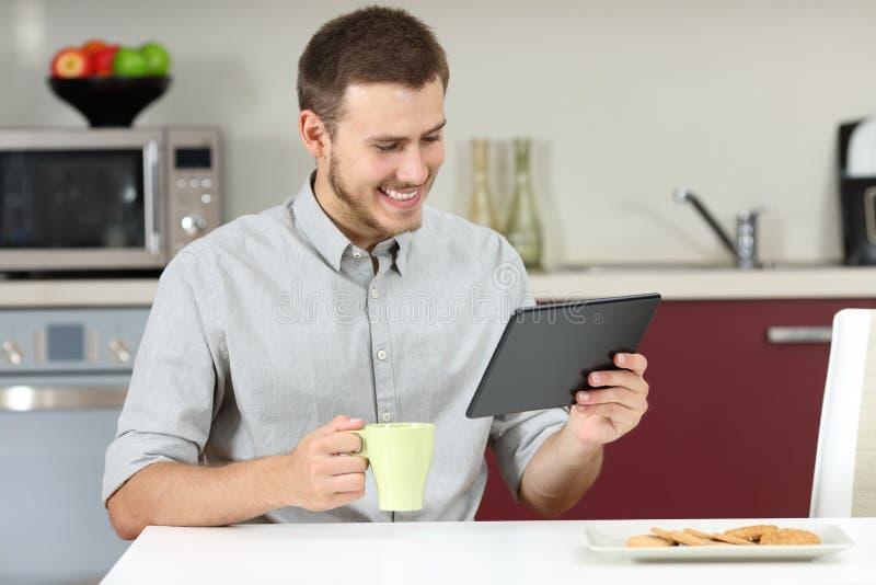 Equipe a notícia da leitura em uma tabuleta no café da manhã fotos de stock royalty free