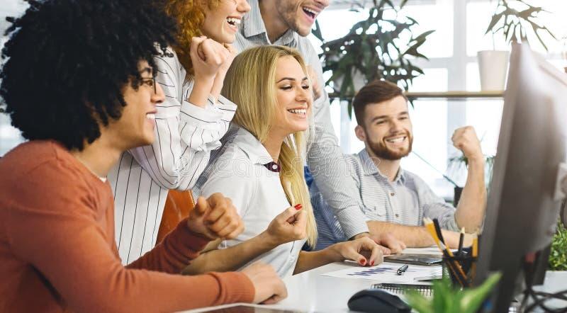 Equipe nova alegre que comemora o sucesso, olhando o computador foto de stock royalty free