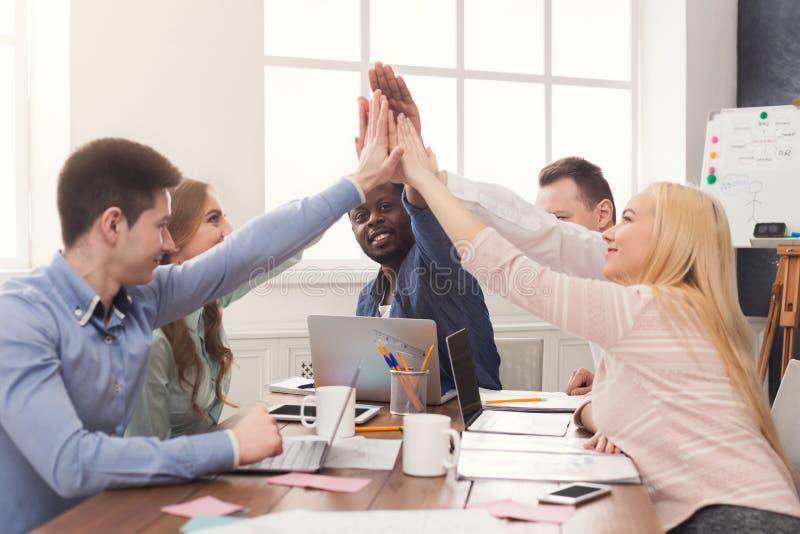 A equipe nova bem sucedida do negócio está dando a elevação cinco imagens de stock royalty free
