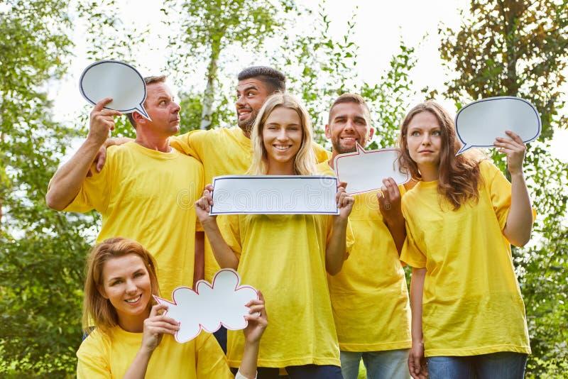 A equipe nova da partida está guardando sinais das bolhas do discurso fotografia de stock royalty free