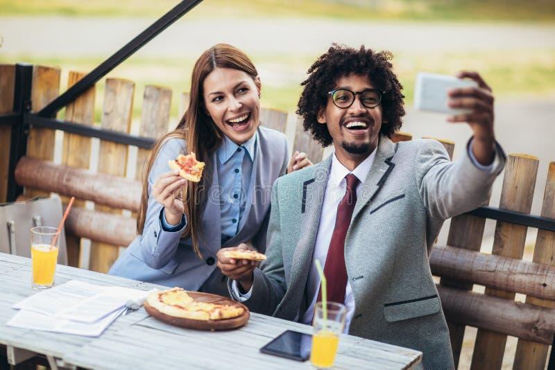 A equipe nova do neg?cio que come a pizza no caf? exterior faz a foto do selfie Conceito do neg?cio, do alimento e dos povos fotos de stock