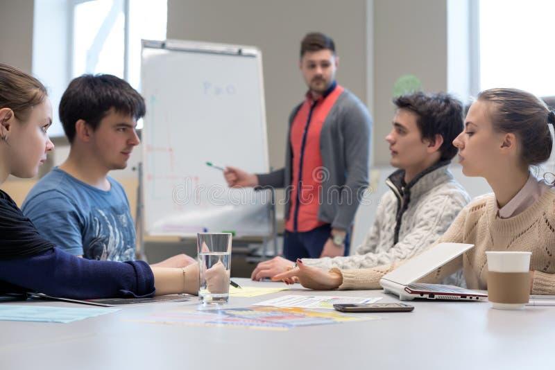 Equipe nova do negócio que discute na tabela cinzenta com Flip Chart fotografia de stock