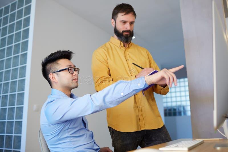 Equipe nova do negócio que trabalha com o escritório coworking moderno do projeto novo da partida Computadores de secretária n imagem de stock