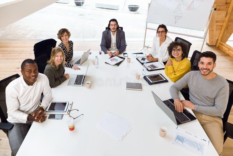 Equipe nova do negócio que trabalha junto e que olha a câmera no lugar coworking fotografia de stock royalty free