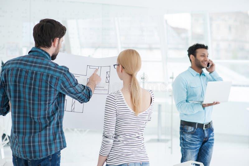 Equipe nova dos arquitetos que trabalham junto no escritório fotografia de stock