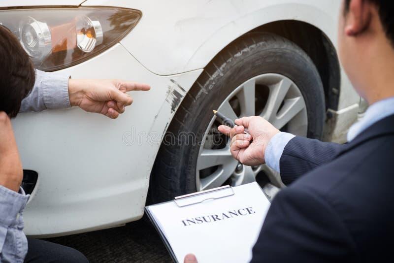 Equipe o agente carro próximo danificado e de exame de Filling Insurance Form, imagem de stock