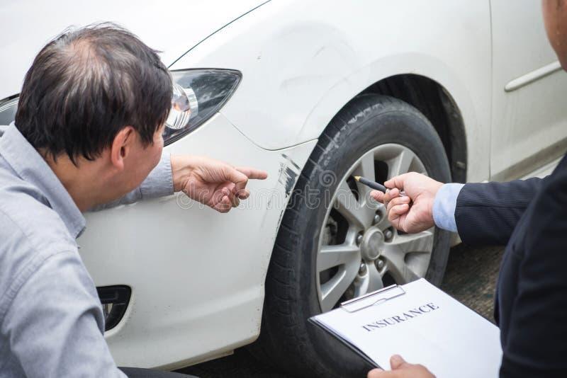 Equipe o agente carro próximo danificado e de exame de Filling Insurance Form, imagem de stock royalty free