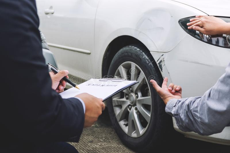 Equipe o agente carro próximo danificado e de exame de Filling Insurance Form, fotografia de stock