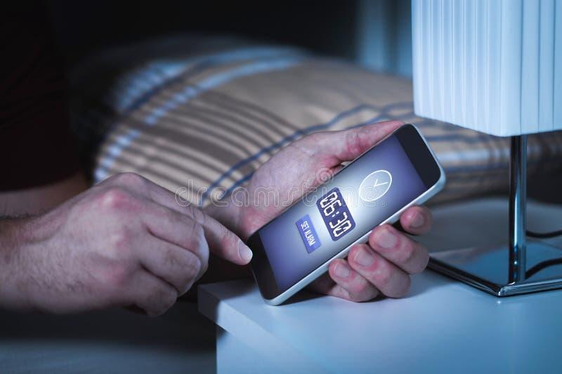 Equipe o alarme do ajuste ao smartphone antes de ir dormir na noite imagens de stock royalty free
