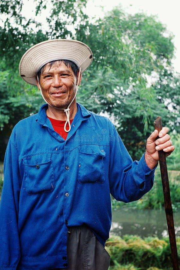 equipe o arroz de colheita e de limpeza ao lado de um rio na parte rural do país foto de stock royalty free
