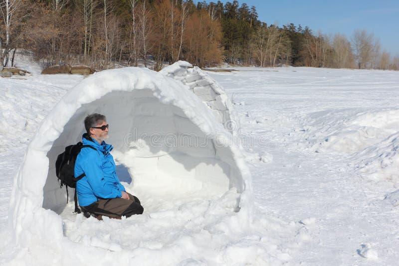 Equipe o assento em inacabado de um iglu em uma clareira imagens de stock royalty free