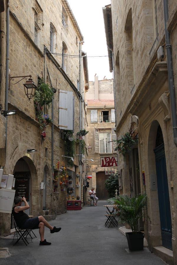 Equipe o assento em um banco em uma rua na cidade de Pezenas, França imagens de stock royalty free