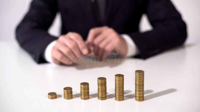 Equipe o assento na frente das pilhas da moeda, a renda do depósito ou o investimento bem sucedido fotos de stock royalty free