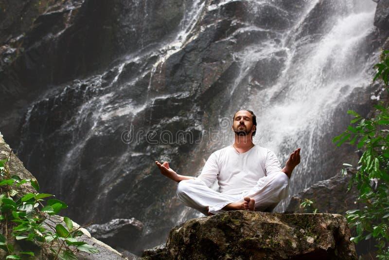 Equipe o assento na ioga da meditação na rocha na cachoeira em tropical imagens de stock royalty free