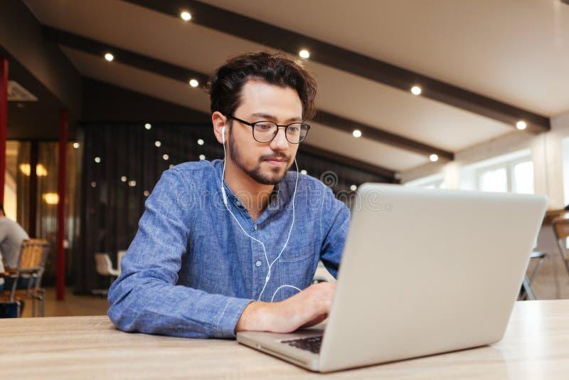 Equipe o assento na tabela com o portátil no escritório imagem de stock