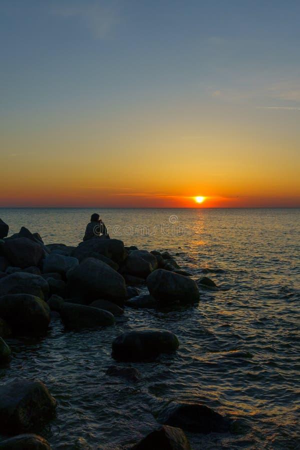 Equipe o assento nas pedras no litoral foto de stock royalty free