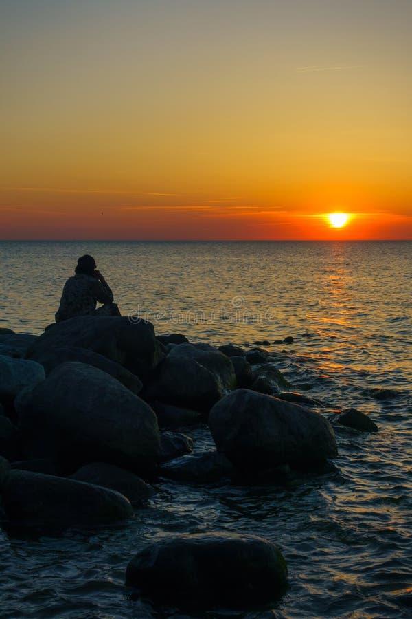 Equipe o assento nas pedras no litoral imagem de stock