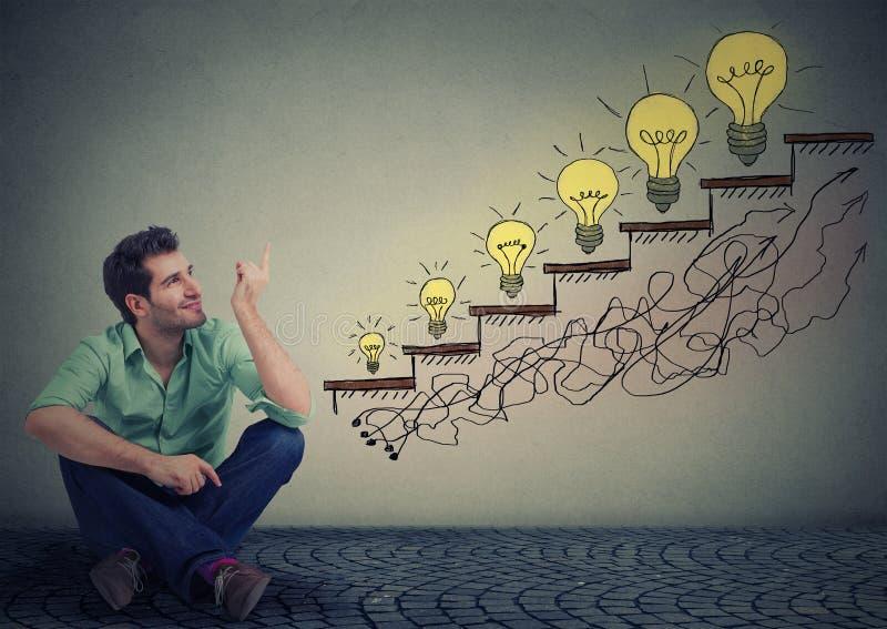 Equipe o assento no assoalho no escritório que aponta no sucesso da educação do negócio, promoção, crescimento da empresa imagens de stock