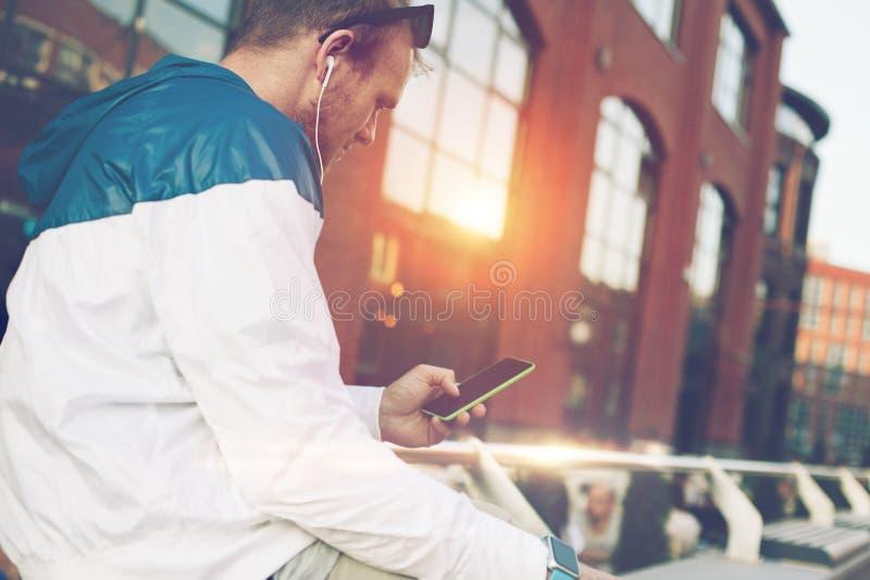Equipe o assento no banco com telefone celular e mensagem de datilografia fotografia de stock royalty free