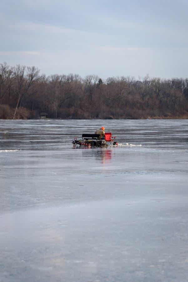 Equipe o assento no banco que a pesca sozinha do gelo fozen sobre o lago no inverno foto de stock