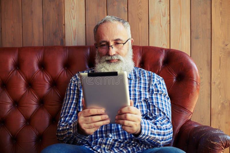 Equipe o assento no sofá e a leitura da notícia em seu PC da tabuleta imagem de stock