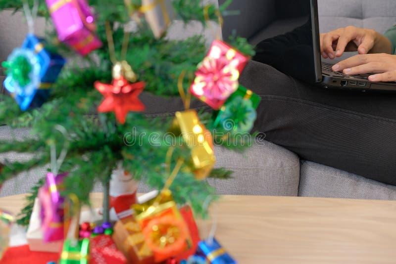 equipe o assento no sofá usando o computador durante o xmas Holida do Natal imagens de stock