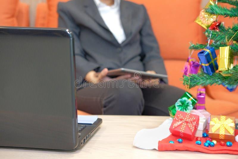 equipe o assento no sofá usando a tabuleta durante o xmas Feriado do Natal fotos de stock royalty free