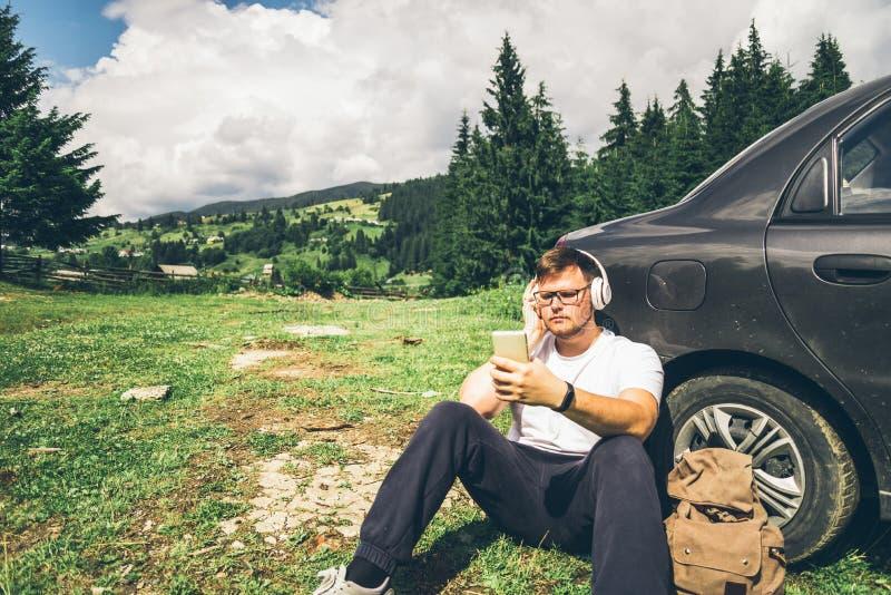 Equipe o assento perto do carro nas montanhas e na música de escuta imagens de stock royalty free