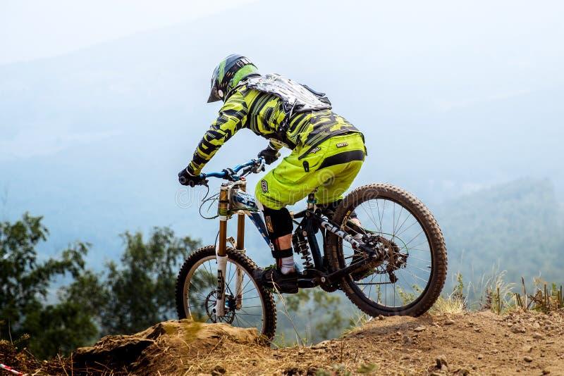 equipe o atleta extremo na descida da bicicleta da parte superior da montanha fotografia de stock