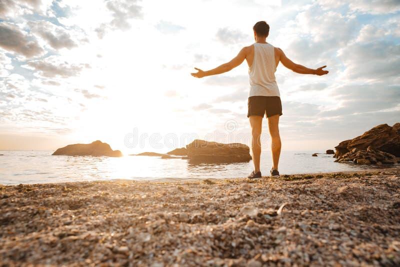Equipe o atleta que está com os braços aumentados e que olha o por do sol imagens de stock