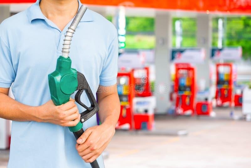 Equipe o bocal de combustível da posse para adicionar o combustível no carro no posto de gasolina fotografia de stock royalty free