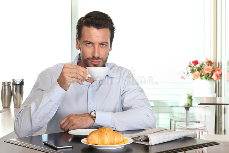 Equipe o café bebendo no café com croissant e jornal no tabl imagens de stock royalty free