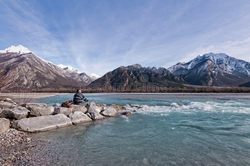 Equipe o caminhante na costa do rio que olha as montanhas fotos de stock royalty free