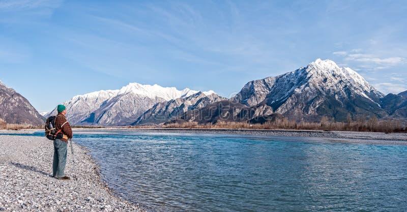 Equipe o caminhante na costa do rio que olha as montanhas imagens de stock royalty free