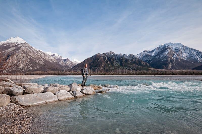 Equipe o caminhante na costa do rio que olha as montanhas foto de stock
