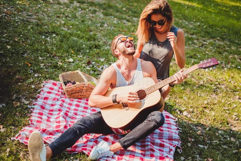 Equipe o canto a sua amiga em um piquenique imagem de stock royalty free